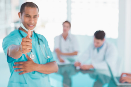 Smiling male surgeon gesturing thumbs up with group around table in background at hospital photo