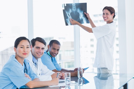 Smiling female doctor explaining x-ray to her team during a meeting photo
