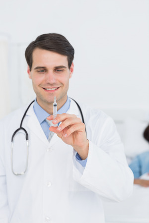 Portrait of a handsome male doctor holding an injection in the hospital photo