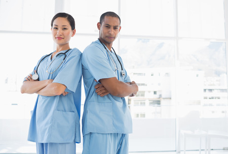Portrait of two confident surgeons standing back to back in the hospital photo