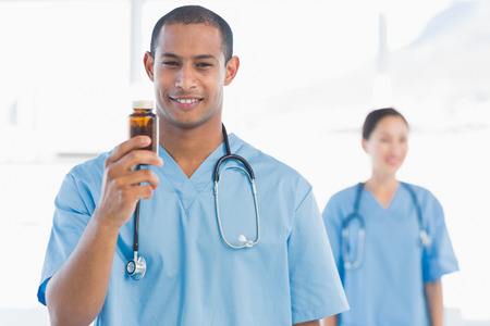 Smiling doctor holding a bottle of pills with colleague in background at hospital photo