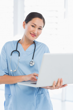 Portrait of a smiling female surgeon using a laptop in a bright hospital Stock Photo - 27048882