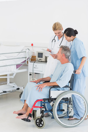 Side view of a doctor talking to a male patient in wheelchair at the hospital photo