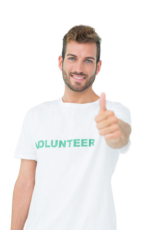 Portrait of a happy male volunteer gesturing thumbs up over white background Stock Photo