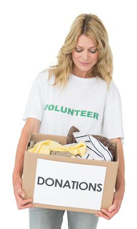altruism: Sonriente mujer joven que lleva a la donación de ropa más de fondo blanco Foto de archivo