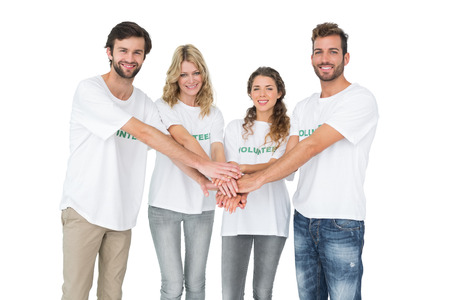 volunteerism: Group portrait of happy volunteers with hands together over white background