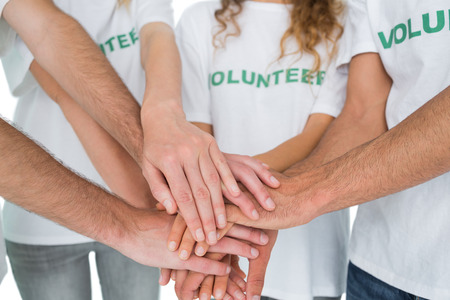 activist: Close-up mid section of volunteers with hands together over white background Stock Photo