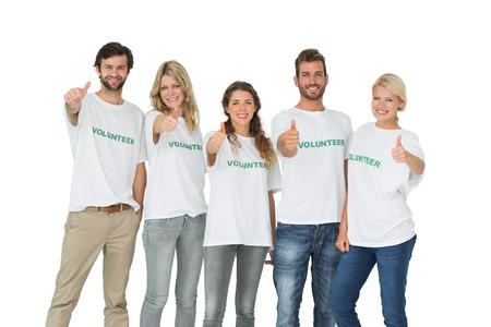 altruism: Retrato del grupo de voluntarios felices que gesticulan los pulgares para arriba sobre fondo blanco