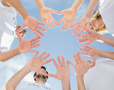 Low angle view of volunteers with hands together against blue sky