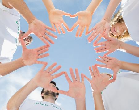 altruism: Ángulo de visión baja de los voluntarios con las manos juntas contra el cielo azul Foto de archivo