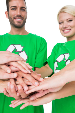 Portrait of young people in recycling symbol t-shirts with hands together over white background