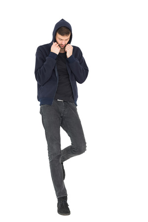 Full length of a stressed handsome young man standing over white background photo
