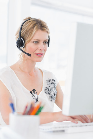 Casual young woman with headset using computer in a bright office photo