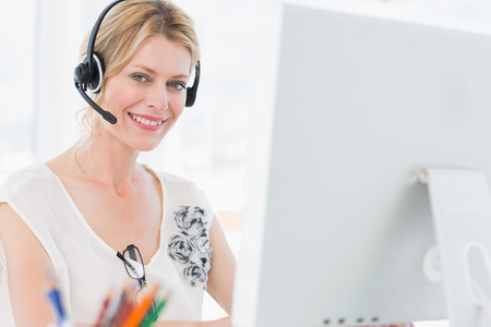 Portrait of a casual young woman with headset using computer in a bright office photo