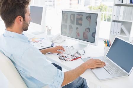 oficina trabajando: Vista lateral de un editor de fotos en masculino para trabajar en equipo en una oficina brillante