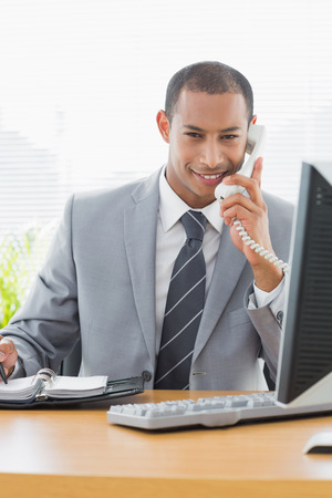 Portrait of a smiling young businessman using computer and phone at office desk photo