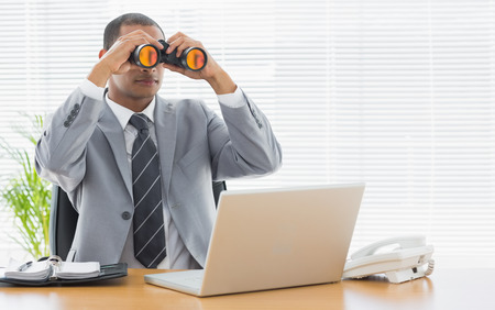 Serious young businessman looking through binoculars in front of laptop at office desk photo