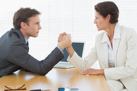 Side view of serious young business couple arm wrestling at office desk photo