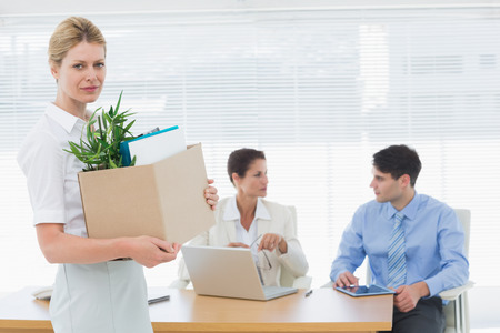 Portrait of a young businesswoman leaving office with her belongings and colleagues in background photo