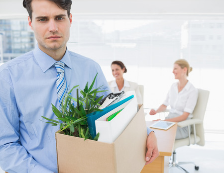 unemployed dismissed: Portrait of a young businessman leaving office with his belongings and colleagues in background