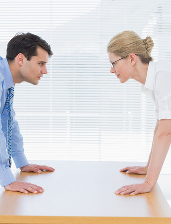 standoff: Side view of serious young business couple looking at each other with palms at the office desk Stock Photo