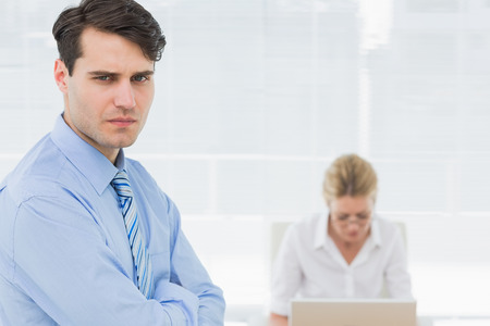 Portrait of a serious confident young businessman with woman working behind at office photo