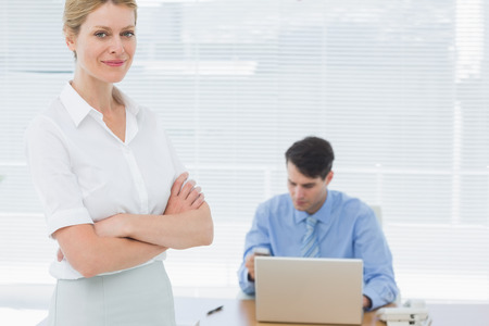 Portrait of a smiling confident young businesswoman with man working behind at office photo