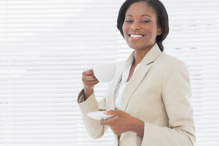Portrait of an elegant young smiling businesswoman with a cup of tea in the office photo