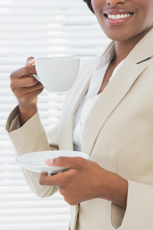 Close-up mid section of an elegant young smiling businesswoman with a cup of tea in the office photo