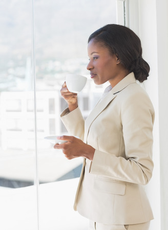 african american woman business: Side view of an elegant young businesswoman with tea cup looking through window in the office