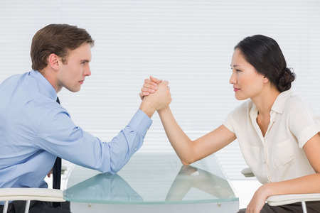 Side view of serious young business couple arm wrestling at office desk Stock Photo - 27051054