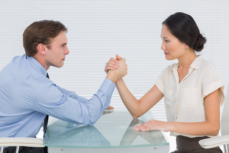 standoff: Side view of serious young business couple arm wrestling at office desk Stock Photo