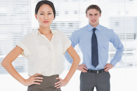 Portrait of two business colleagues standing with hands on hips in the office photo