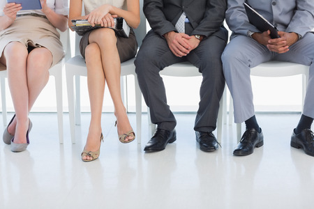 Low section of business people waiting for job interview in a bright office photo
