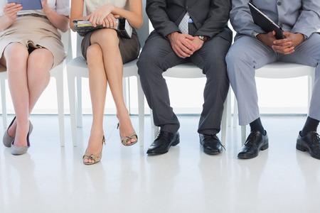 file d attente: Section basse de gens d'affaires en attente pour une entrevue d'emploi dans un bureau lumineux