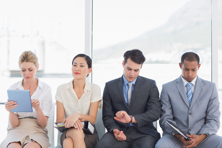Four business people waiting for job interview in a bright office photo