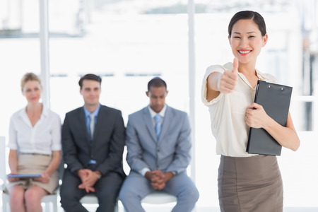 Portrait of a young woman gesturing thumbs up with people waiting for job interview in a bright office photo