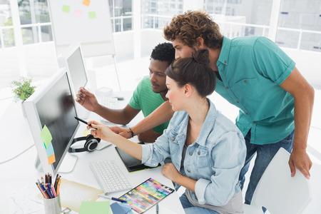 사무실 컴퓨터에서 작동하는 세 아티스트의 측면보기