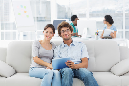Casual couple using digital tablet with colleagues in background at a creative bright office photo