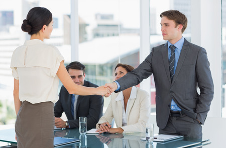Handshake to seal a deal after a job recruitment meeting in an office photo