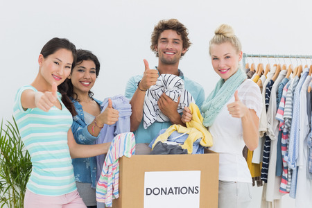 Group of young people with clothes donation gesturing thumbs up photo