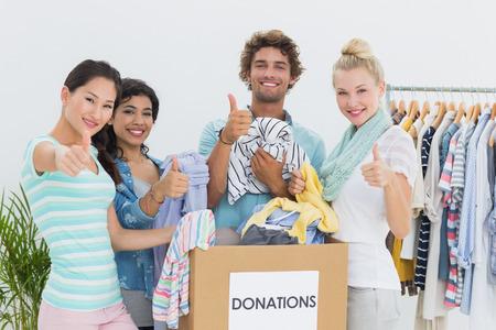 altruismo: Grupo de j�venes con la donaci�n de ropa que gesticula los pulgares para arriba