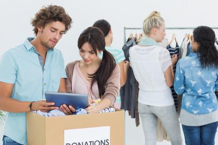 altruismo: Grupo de j�venes con la donaci�n de ropa, mientras que usa la tablilla digital Foto de archivo