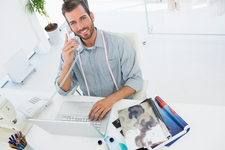 Young male fashion designer using laptop and phone in the studio photo
