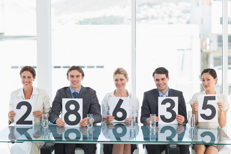 Portrait of a group of panel judges holding score signs