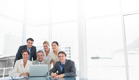 Group of happy business colleagues with laptop at office desk photo