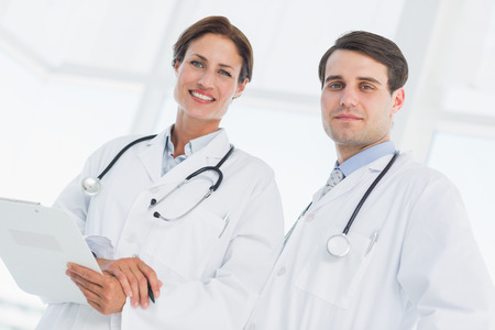 Portrait of a male and female doctors with report in the hospital photo