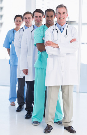 Full length portrait of doctors standing in a row at the hospital photo