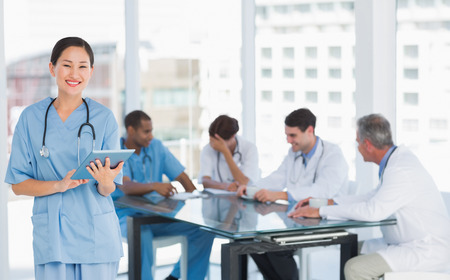 Female surgeon using digital tablet with group around table in background at hospital photo