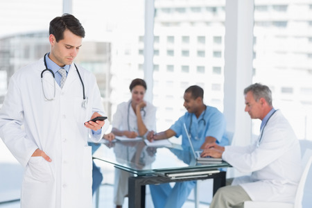 Doctor text messaging with group around table in background at hospital photo